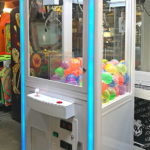This claw machine was wrapped in all white and enhanced with blue corporate light trim.