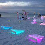 LED illuminated corn hole games on the beach.